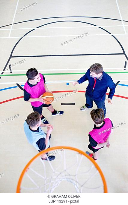 Gym teacher guiding high school students playing basketball in gym class