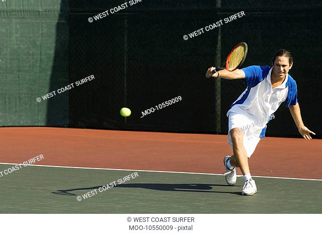 Tennis Player squatting on tennis court Hitting Backhand
