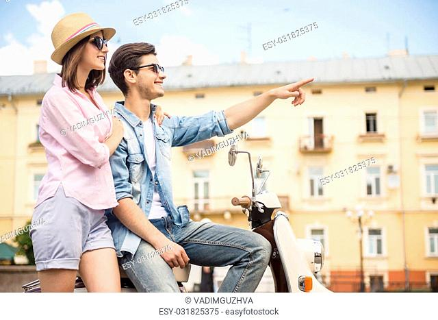 Beautiful young couple dressed casual sitting on scooter together. Side view