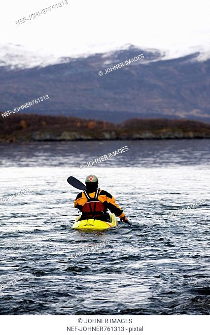 Man paddling in the outlet of a stream, Lapland, Sweden