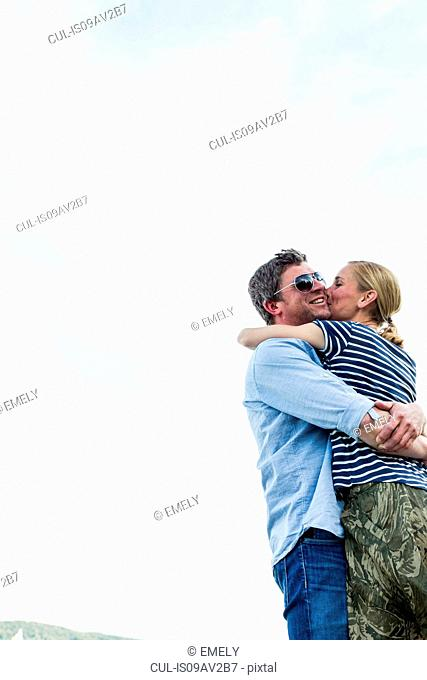 Low angle view of romantic couple hugging and kissing against sky