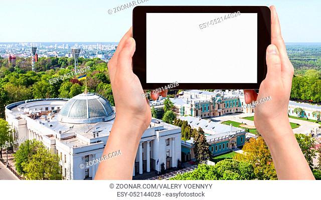 travel concept - tourist photographs Verkhovna Rada building (Supreme Council of Ukraine) and Mariyinsky palace in Mariinsky park in Kiev city on tablet with...