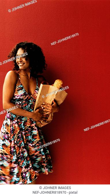 Woman in a dress with a bag full of food