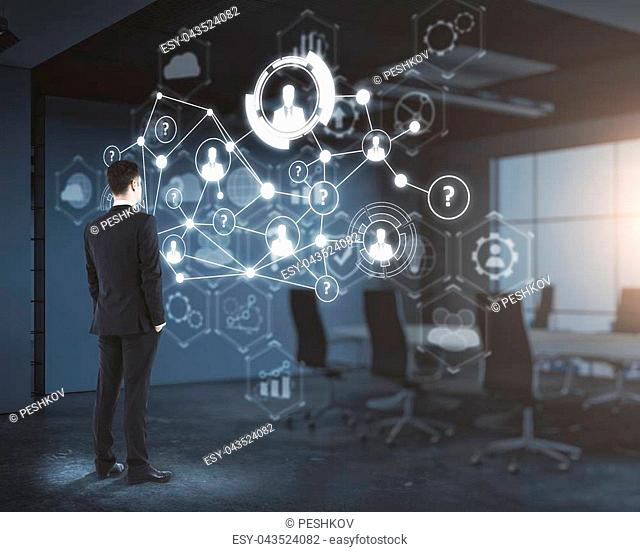 Side view of young businessman looking at digital business interface in blurry office interior. Workplace and innovation concept. Double exposure
