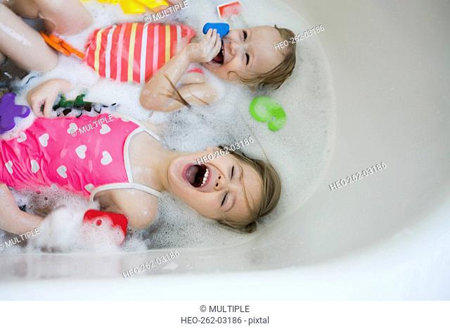 Overhead view sisters laying and laughing bubble bath