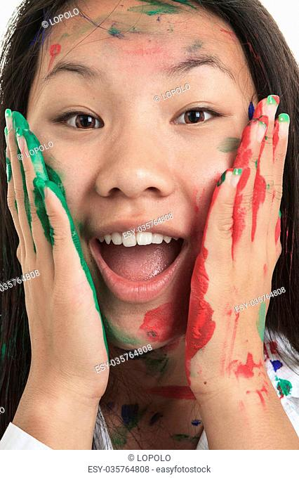 A little asian girl having fun with paint on it isolate on white