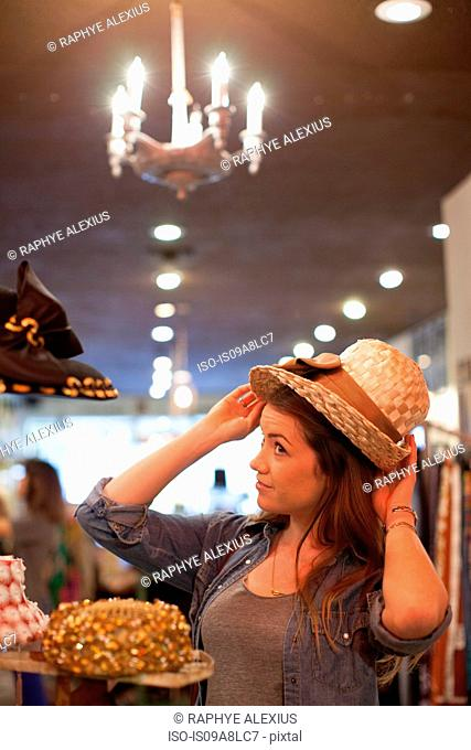 Young woman trying on straw hat in vintage shop