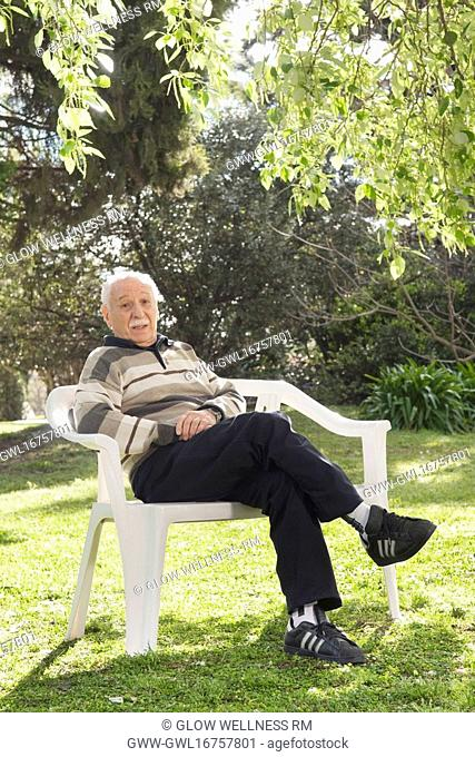 Portrait of a man sitting on a chair in a park