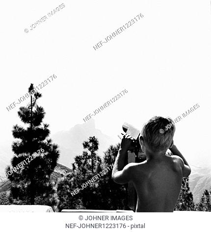 Boy looking at landscape through telescope