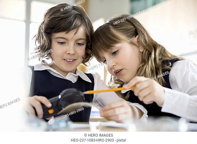 School girls conducting scientific experiment in classroom