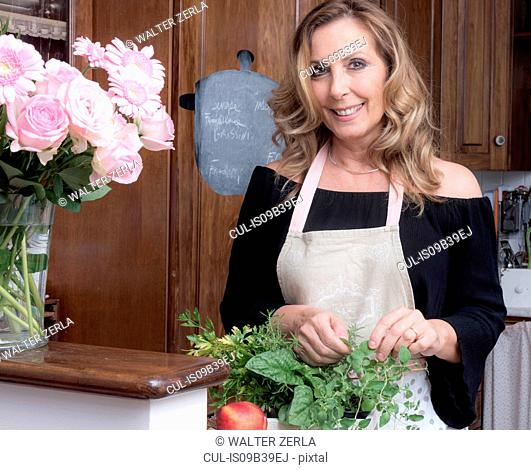 Portrait of mature woman picking fresh herbs plant in traditional Italian kitchen