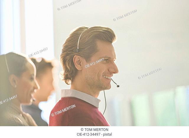 Smiling male telemarketer wearing headset talking on telephone