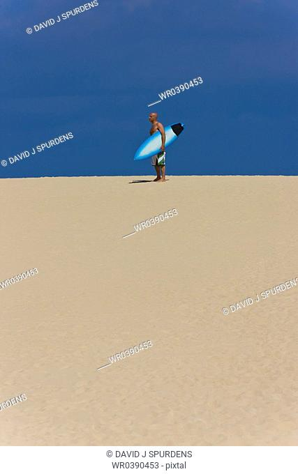 A surfer standing on a sand dune with surfboard
