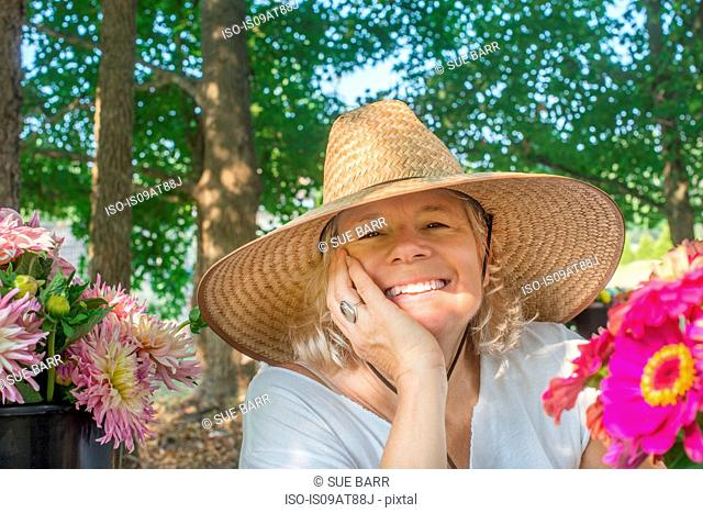 Portrait of senior female farmer wearing sun hat with cut flowers