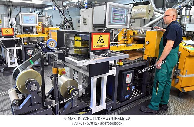 Mechatronic technician Jens Rambow working at a so-called extrusion machine for producing electrodes at EAS Germany GmbH in Nordhausen, Germany, 4 July 2016