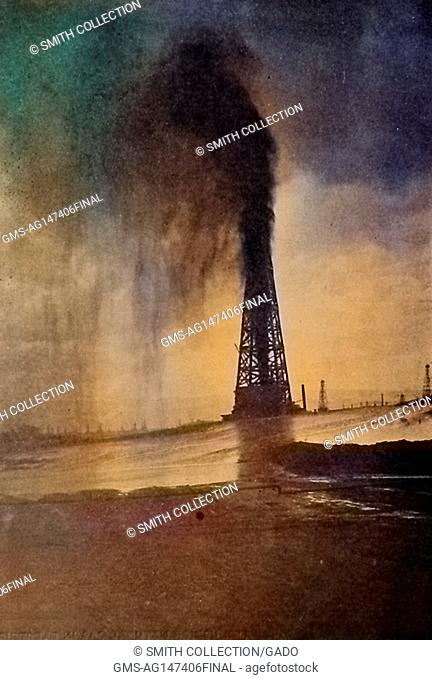 Photograph entitled 'Lakeview Gusher', showing an oil derrick with flowing oil, installed by the Standard Oil company and operating using an electric pumping...
