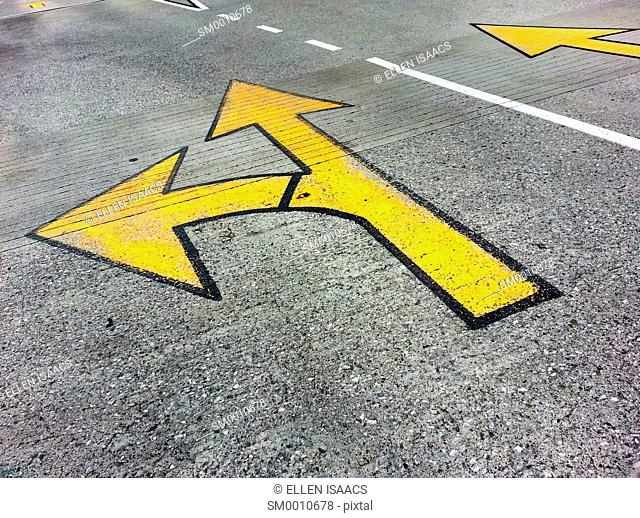 Arrows painting on the road pointing left and straight, indicating a choice or decision