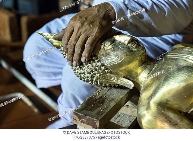 sculptor working on casting Buddha images at Wat Arun, Bangkok, Thailand
