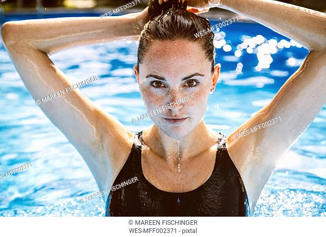 Portrait of female swimmer fixing her hair while standing in swimming pool