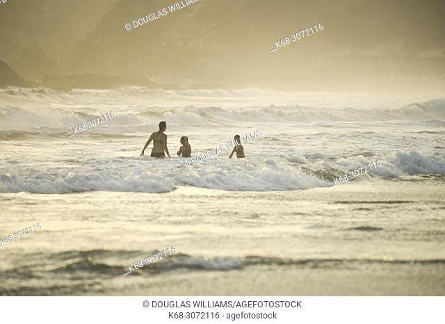 A family in the waves at a beach near San Agustinillo, Oaxaca, Mexico
