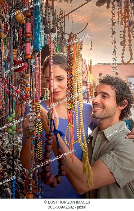 Young couple at market looking at beads, Jemaa el-Fnaa Square, Marrakesh, Morocco