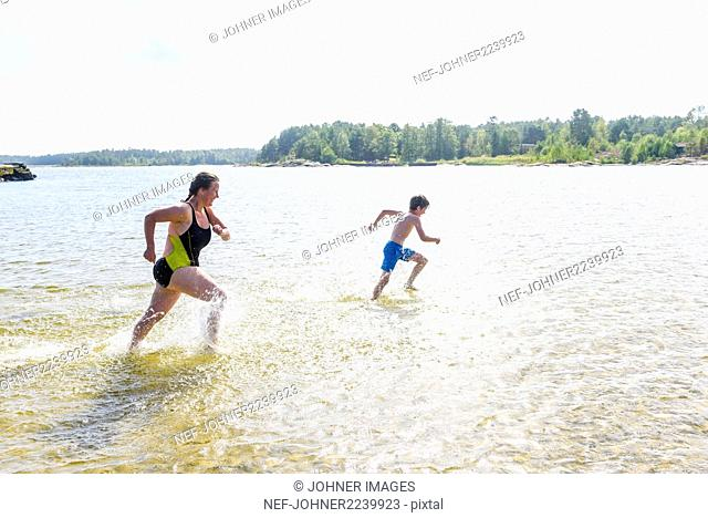 Mother running with son in lake