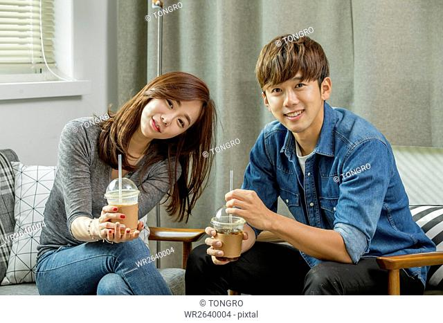 Young smiling couple with takeout coffee resting indoors