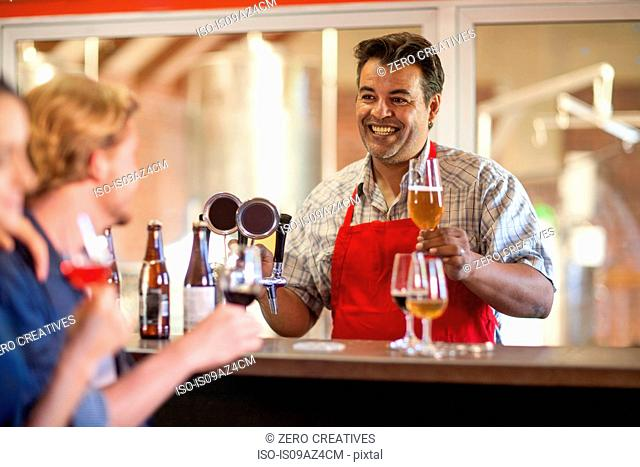 Bartender in public house serving customers beer smiling