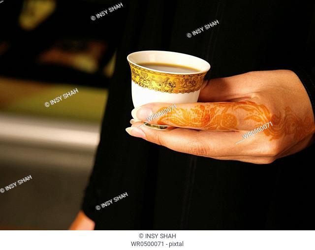 Arab lady with henna on hands holding Arabic Coffee cup