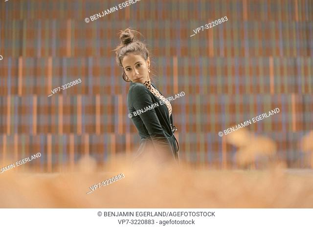 confident fashionable woman posing in front of geometrical pattern, lines, in Munich, Germany