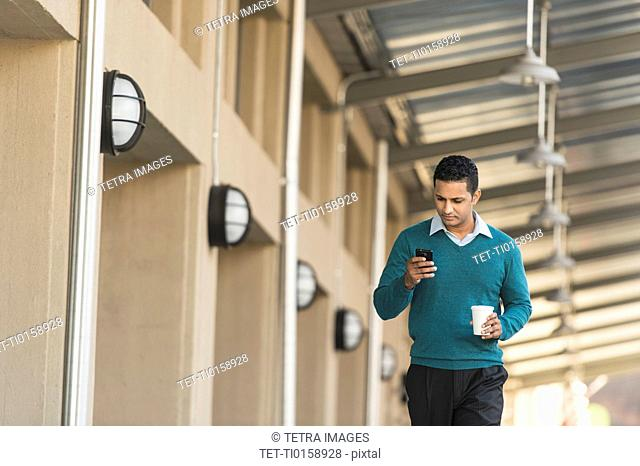 Man walking outside building and text messaging