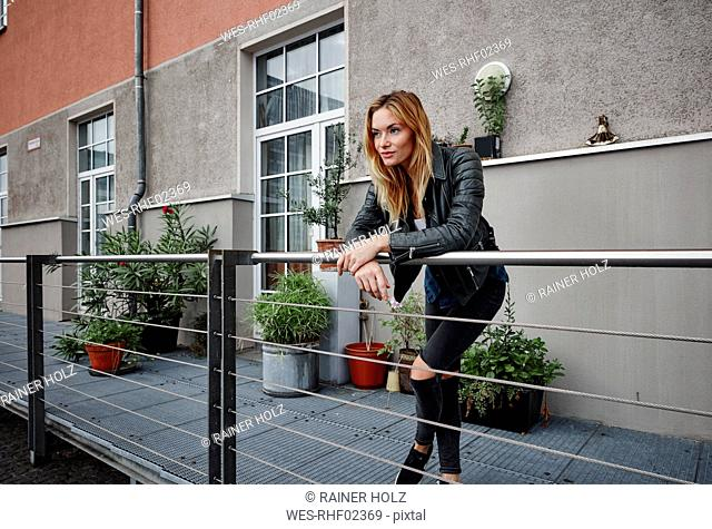 Confident young woman wearing biker jacket leaning on balcony railing