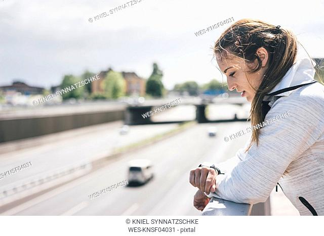 Sportive young woman looking on watch at motorway