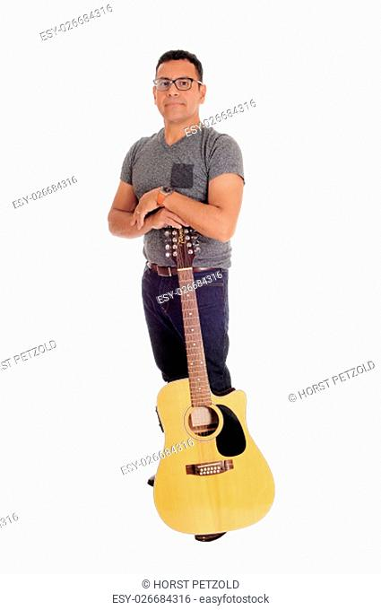 A middle age Hispanic man standing isolated for white background.holding his guitar, looking into the camera.