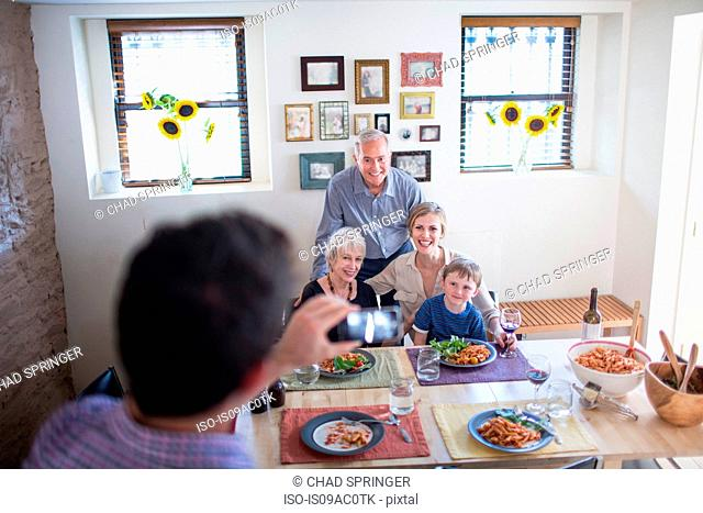 Man photographing family at meal time