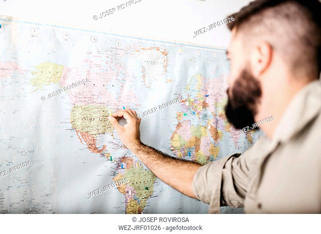 Young man selecting travel destinations on a world map