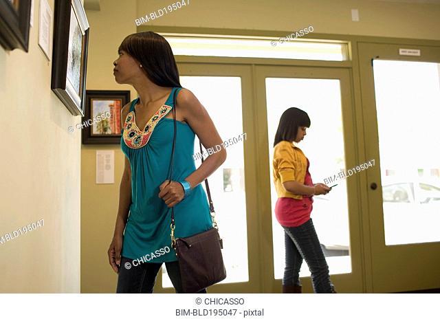 Woman admiring painting in gallery