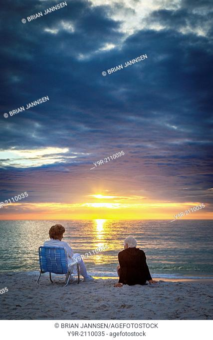 Two elderly women enjoying a sunset on the beach in Naples, Florida, USA