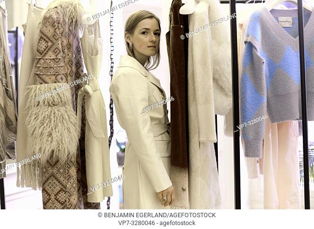 fashionable woman between new fashion collection, blogger in private showroom during fashion week, in Paris, France