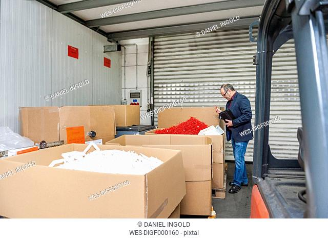 Manager in storage of plastics factory checking products
