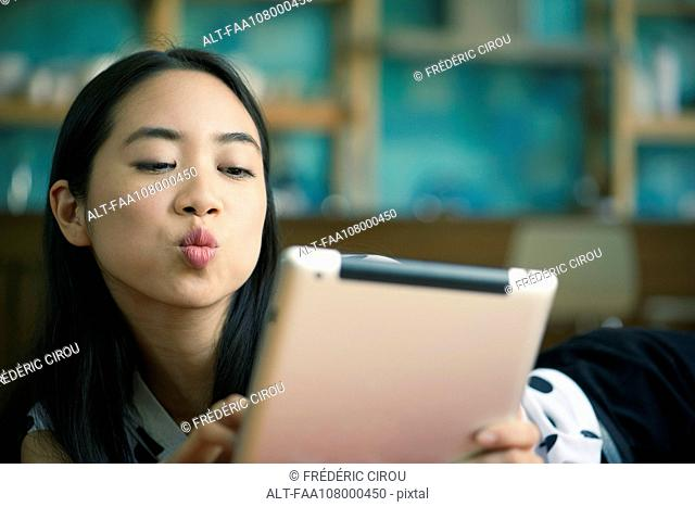 Young woman blowing kiss while video conferencing on digital tablet