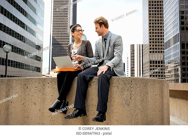 Businessman and woman sitting on wall using laptop, Los Angeles, USA