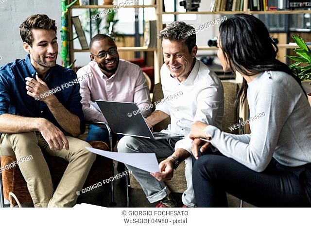 Business team using laptop and discussing documents in loft office