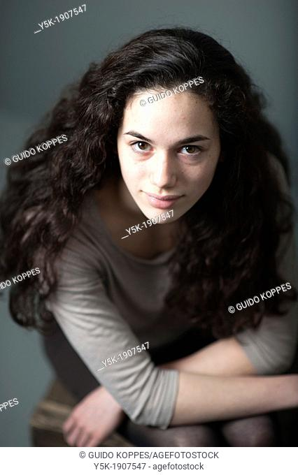 Tilburg, Netherlands  Portrait of a young brunette against a grey background, sitting on a stool