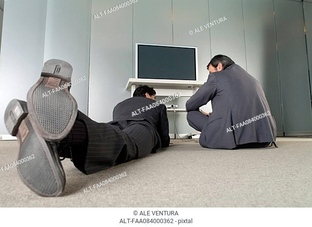 Businessmen relaxing on the floor, rear view