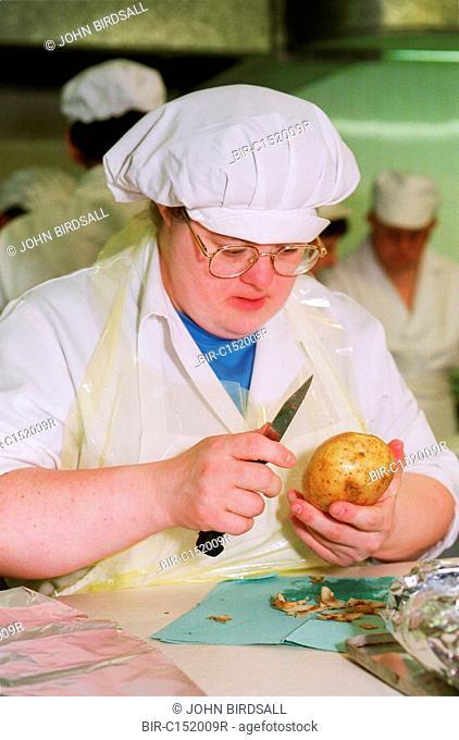 Woman with Downs Syndrome peeling potato