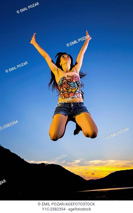 Jumping woman in sunset