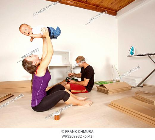 Young Family with a Baby Moving to New Flat