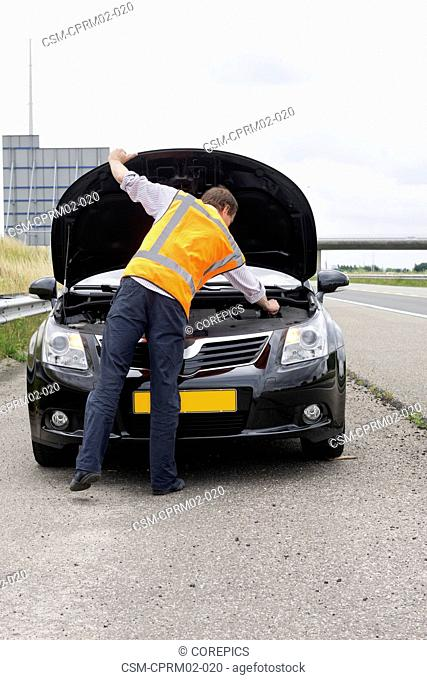 motorist looking under the hood of his stalled car on the hard shoulder of a motorway