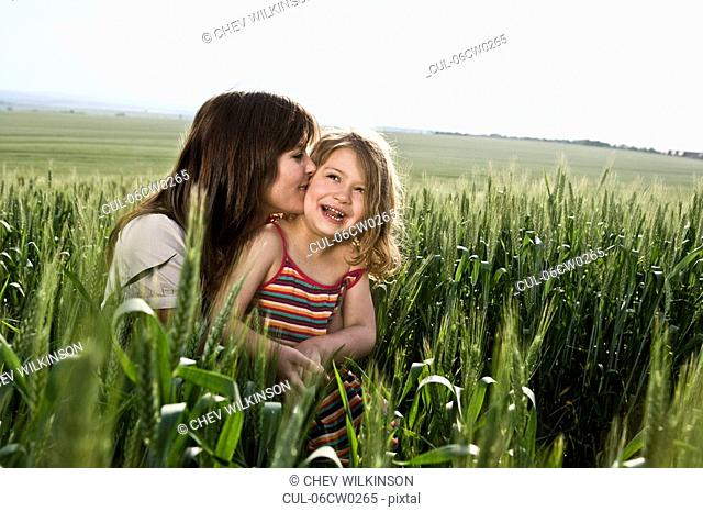 Mother kissing child in wheat field